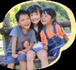 笑顔で頬を寄せ合う3人の子供達