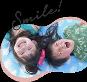 空の模様のシートの上に笑顔で横たわる2人の子供